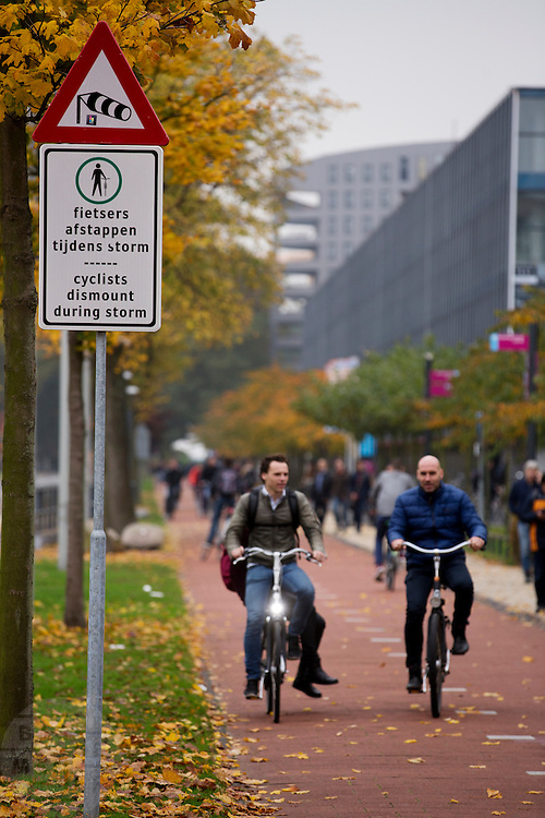 In Delft waarschuwt een bord fietsers voor harde windvlagen die instaan tussen de hoge gebouwen tijdens een storm. Fietsers moeten dan afstappen.<br /> <br /> In Delft a sign warns cyclists for heavy winds at stormy weather. Cyclists have to dismount.