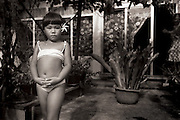 A little girl in a bathing suit and a flower in her hair stands outside of her home in Tahiti.