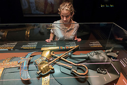 """© Licensed to London News Pictures. 01/11/2019. LONDON, UK. A staff member views gold decorations found on the mummy of Tutankhamun.  Preview of """"Tutankhamun, Treasures of the Golden Pharoah"""" at the Saatchi Gallery in Chelsea.  The exhibition celebrates the 100th year anniversary of the opening of Tutankhamun's tomb and displays 150 works in the largest collection of Tutankhamun's treasures ever to leave Egypt.  The show runs 2 November to 3 May 2020.  Photo credit: Stephen Chung/LNP"""