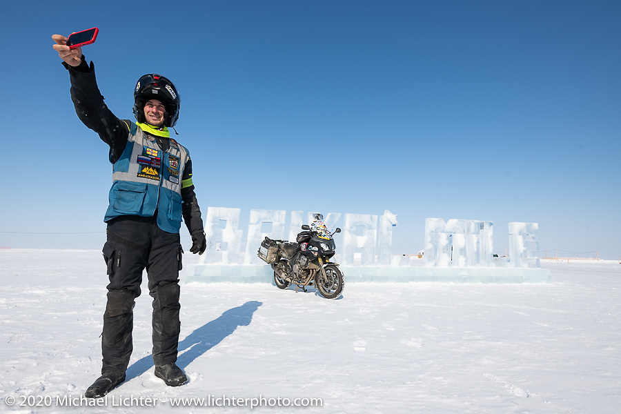 Cold weather adventure motorcyclist and author Alessandro Ciceri, better known as Wizz (@wizz_inwiaggio), after riding 6,200 mile (10,000 km) from his home in Italy in the middle of winter, seen here taking a selfie with the ice sculpture sign at the entrance to the Baikal Mile Ice Speed Festival. Maksimiha, Siberia, Russia. Monday, March 2, 2020. Photography ©2020 Michael Lichter.