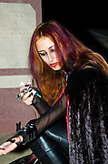 midnight in a cemetery, a gothic dressed female model, using a syringe to inject herself - mock up. Model released shot,