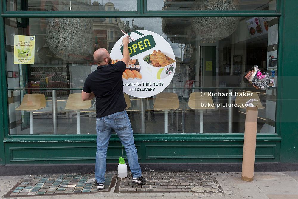 With the Coronavirus pandemic lockdown rules being eased, pubs and restaurant businesses are slowly re-opening and a contractor smooths a over a sticker sign just applied to the window of Wasabi in Shaftesbury Avenue in the capital's West End, on 6th July 2020, in London, England.