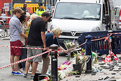 © Licensed to London News Pictures . FILE PICTURE DATED 15/07/2013 . Oldham Street , Manchester , UK . Mum Susan lays flowers at the scene . Stephen Hunt's family at the scene . Son Sam (maroon shorts , 15), brother Christopher (white t-shirt, jeans, close cropped hair), grandmother Ruth (blue check shirt, dark trousers , red sunglasses), mother Susan (blue top, beige slacks, sunglasses), stepfather Wilf (dark hair, black t-shirt, grey shorts), daughter Charlotte (black and white sleeveless top, black pants, 18), sister Sarah (cream sleeveless top, blue jeans, dark hair, sunglasses) and ex-wife Zoe (white top, black pants, sunglasses) . The scene on Oldham Street following a fire at Paul 's Hair World on 13th July which claimed the life of fireman Stephen Hunt . Photo credit : Joel Goodman/LNP