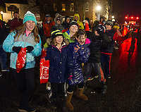 The rain didn't dampen the spirit for families along Main Street during the annual Holiday Parade through downtown on Saturday evening.  (Karen Bobotas/for the Laconia Daily Sun)