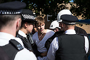 Bailiffs and police officers speak to a housing activist evicted from a property on the Sweets Way housing estate on 23rd September 2015 in London, United Kingdom. A group of housing activists calling for better social housing provision in London had occupied some of the properties on the 142-home estate in Whetstone, in some cases refurbishing properties intentionally destroyed by the legal owners following eviction of the original residents, in order to try to prevent the eviction of the last resident on the estate and the planned demolition and redevelopment of the entire estate by Barnet Council and Annington Property Ltd.
