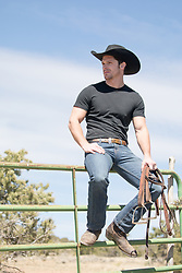 cowboy sitting on a ranch gate with reins in his hand