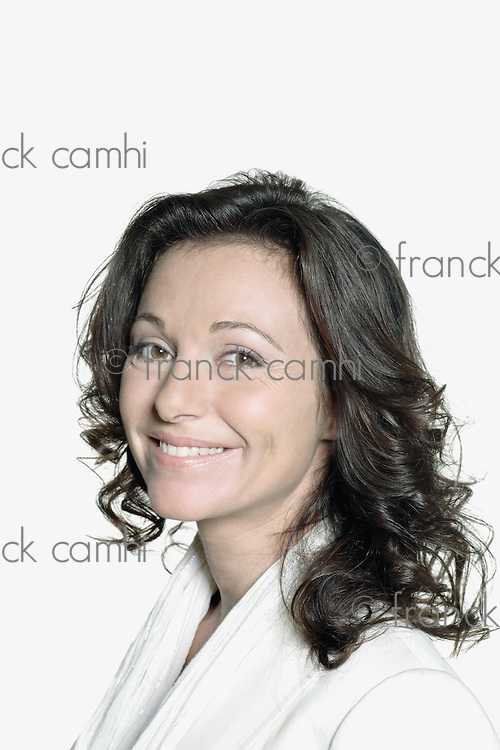 portrait on white background of a forty years old woman in studio smiling wearing a white vest
