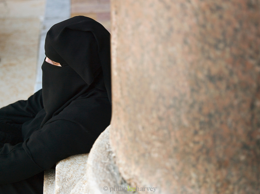 A woman sits in the grounds the Umayyad Mosque, the Great Mosque of Damascus, Damascus, Syria