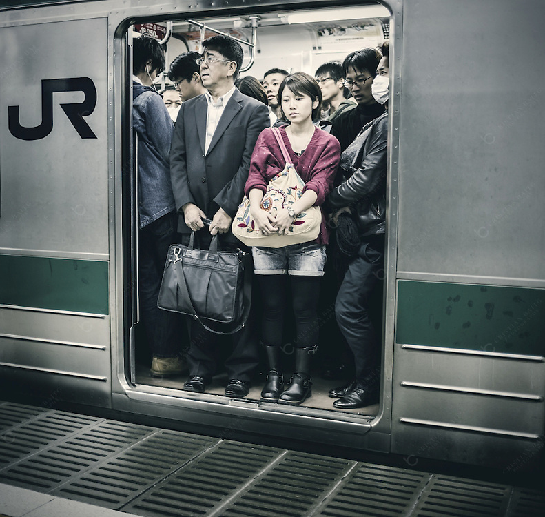 Passengers inside JR subway  train in Tokyo Japan. It is considered the most used subway system in the world with more than 6 million users daily and 179 stations.