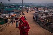 A man smokes a cigarette as he walks in the early hours of the morning in the Balukhali refugee camp in Cox's Bazar, Bangladesh, December 3, 2019. For the past 40 years, Bangladesh has provided shelter to Rohingya refugees from Myanmar following five separate outbreaks of violence and persecution. Prior to the most recent outbreak of violence in 2017, close to 200,000 Rohingya refugees already lived in Cox's Bazar District. This placed additional pressure on the already fragile social and economic structure of Cox's Bazar, one of the worst performing districts in Bangladesh in almost all child-related indicators and one of the most vulnerable to disasters and climate change. The latest violence and persecution against Rohingya erupted on 25 August 2017, prompting 740,000 Rohingya refugees to flee their homes in Myanmar and seek safety in Bangladesh. There are now close to one million Rohingya refugees living in crowded congested camps in Cox's Bazar. Women and children comprise 80 per cent of the population, over 500,000 are children under the age of 18.