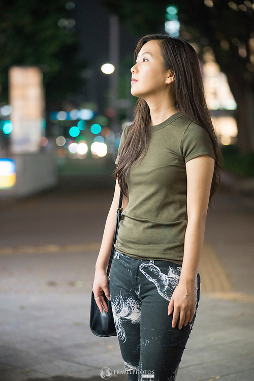 Young Japanese lady in the trendy part of Nagoya city at night.