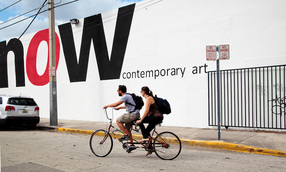 A couple rides a bicycle built for two past the giant NOW art gallery sign in Miami's Wynwood district.