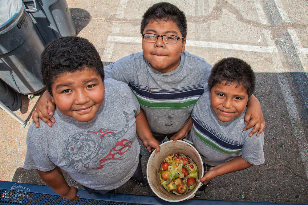Young boys collect food for the worm compost bin after their class mates eat their lunch at the Downtown Value School, a charter school in downtown Los Angeles.