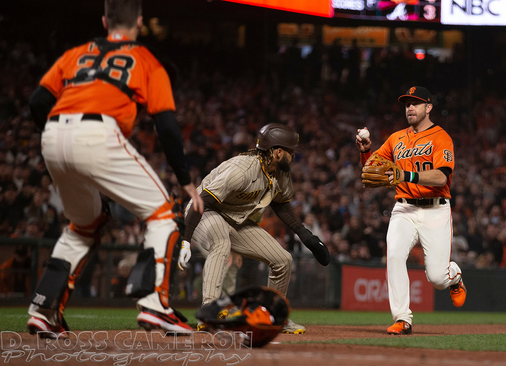 Oct 1, 2021; San Francisco, California, USA; San Diego Padres shortstop Fernando Tatis Jr. (23) is caught in a rundown between San Francisco Giants third baseman Evan Longoria (10) and catcher Buster Posey after overrunning third on an infield single by Eric Hosmer during the sixth inning at Oracle Park. Mandatory Credit: D. Ross Cameron-USA TODAY Sports