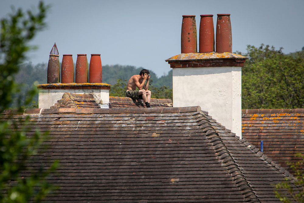 A male roofer sits on a house roof top during a break on the 21st of July 2021 in Folkestone, Kent, United Kingdom. Roofing is one of the most dangerous professions, some roofers in the UK still work without the correct safety equipment. (photo by Andrew Aitchison / In pictures via Getty Images)