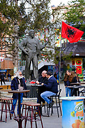 Men sit outside drinking and smoking next to the Albanian flag and a statue of  Mehë Uka in the shopping area in the south side of Mitrovica, a town in Northern Kosovo that straddles the river Ibar that separates the Serbian and Albanian districts of Mitrovica, Kosovo on the 12th of December 2018.  Meha Uka was a teacher, political prisoner, who is  a Hero of Kosovo. Mitrovica or Kosovska Mitrovica is a city and municipality located in Northern Kosovo.