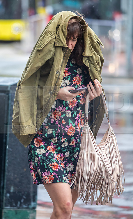 © Licensed to London News Pictures. 19/08/2020. London, UK. A women gets caught in heavy rain with gusty winds in Westminster today as weather forecasters predict a warmer and sunnier week ahead with highs of 24c . Photo credit: Alex Lentati/LNP