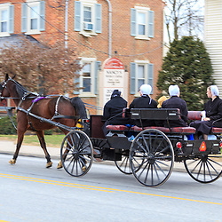 Intercourse, PA - December 1, 2014: Amish women ride in a tall wagon on the Old Philadelphia Pike in the Lancaster County village.
