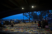 People searching for books at the second hand book stalls underneath Waterloo Bridge on the Southbank, London, United Kingdom. The South Bank is a significant arts and entertainment district, and home to an endless list of activities for Londoners, visitors and tourists alike.