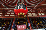 A woman views the ornate red-paper lantern over the entrance to the main hall of the Sensoji Buddhist temple in Asakusa, Tokyo, Japan. The temple was built during the Kamakura period in 645 CE and is the oldest and most important temple in Tokyo.