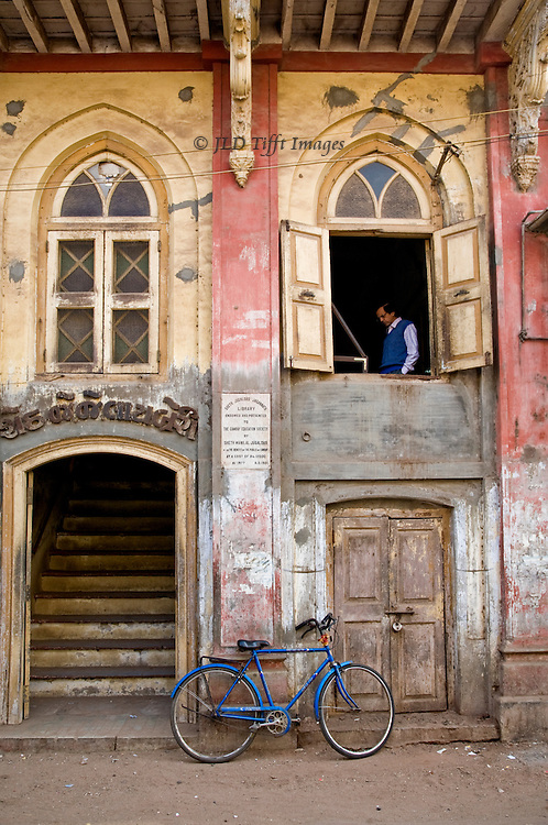 Street scene in Khambat, Gujarat, India, showing facade of the town library, reader seen through open window; bicycle leaning against the wall.
