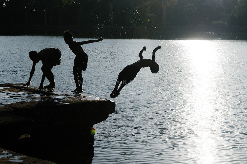 Boys jumping into the moot near the entrance of Angkor Wat, Angkor temple complex, Cambodia