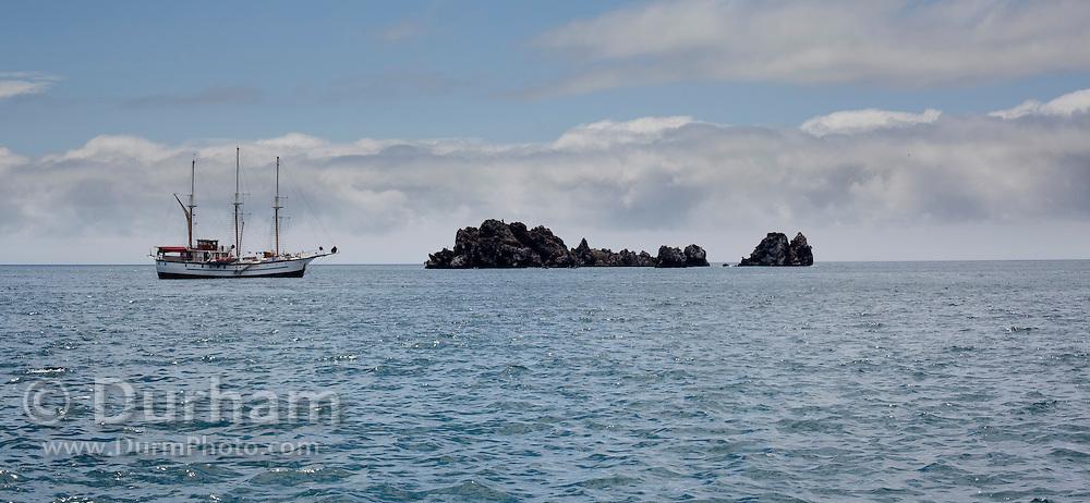 A masted sailing ship cruising through the waters near Floreana Island, the Galapagos Archipelago - Ecuador.
