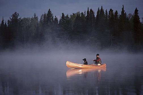 Canoeist with balck lab in canoe paddling across small lake. Foggy, morning. Northern Minnesota.
