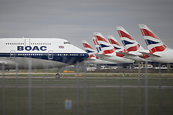 """© Licensed to London News Pictures. 17/03/2020. London, UK. A British Airways 747 Jumbo, painted in BOAC colours, taxis past a line of parked aircraft at Heathrow's Terminal Five. The Airport Operators Association has said that UK airports will shut down within weeks without government support. The government have advised the public that they should avoid """"non-essential"""" travel and contact with others to curb the spread of the coronavirus. Photo credit: Peter Macdiarmid/LNP"""