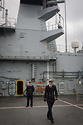 Two student officers on duty on the top deck during a tour by the general public on-board the Royal Navy's aircraft carrier HMS Illustrious during a public open-day in Greenwich. Illustrious docked on the river Thames, allowing the tax-paying public to tour its decks before its forthcoming decommisioning. Navy personnel helped with the PR event over the May weekend, historically the home of Britain's naval fleet.