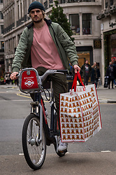 © Licensed to London News Pictures. 12/12/2020. LONDON, UK.  A shopper with a large shopping bag rides a hire bicycle in Regent Street as the number of coronavirus cases rises in the capital.  Retailers are hoping that physical sales will pick up in the run up to Christmas.  This comes against a backdrop of two major retailers Debenhams and Arcadia, owner of Topshop, collapsing into administration in recent weeks.  Photo credit: Stephen Chung/LNP