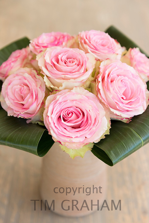 Lace-edged attractive pastel pink roses in an elegant bouquet style floral arrangement with banana leaves in terracotta vase