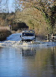 © Licensed to London News Pictures. Date 24 December 2013. Ascott Under Wychwood. Land Rover drives down flooded road at Ascott Under Wychwood. Flooding images - River Evenlode in full flood.. Photo credit : MarkHemsworth/LNP