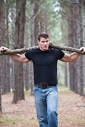 man walking in the woods with a large tree branch on his shoulders