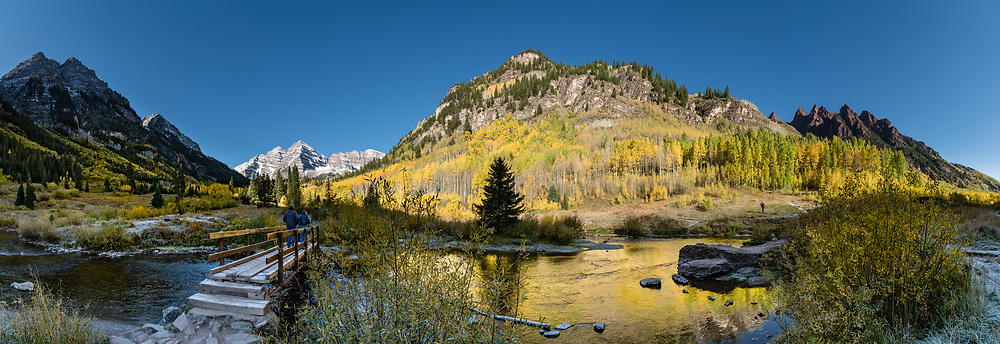 Morning light spotlights the Maroon Bells as yellow aspen leaves reflect in Maroon Creek. The Maroon Bells are two adjacent peaks of the Elk Mountains: snow-covered Maroon Peak 14,163 feet on left, seen behind adjacent North Maroon Peak 14,019 feet, in Maroon Bells-Snowmass Wilderness of White River National Forest. The mountains are on the border between Pitkin County and Gunnison County, 12 miles southwest of Aspen, in Colorado, USA. This image was stitched from multiple overlapping photos.