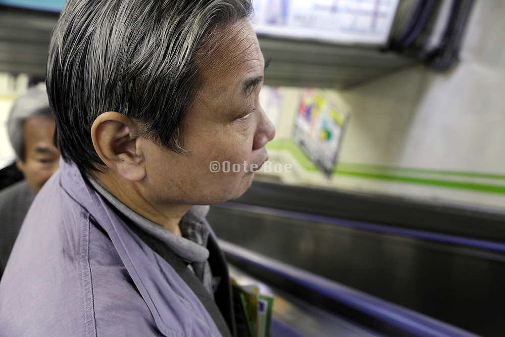 senior Asian male person on escalator Japan