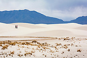 Visitors stroll on the gypsum dunes of White Sands National Monument, New Mexico