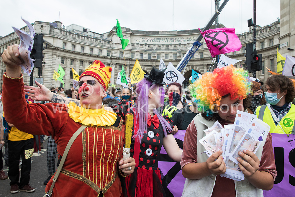 London, UK. 3rd September, 2020. A troupe of clowns holding banknotes joins fellow climate activists from Extinction Rebellion at a 'Carnival of Corruption' protest against the government's facilitation and funding of the fossil fuel industry. Extinction Rebellion activists are attending a series of September Rebellion protests around the UK to call on politicians to back the Climate and Ecological Emergency Bill (CEE Bill) which requires, among other measures, a serious plan to deal with the UK's share of emissions and to halt critical rises in global temperatures and for ordinary people to be involved in future environmental planning by means of a Citizens' Assembly.