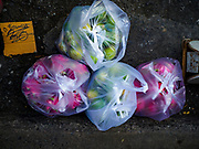 20 JUNE 2018 - BANGKOK, THAILAND: A customer's purchases in plastic bags at Makkasan Market, a small local market in central Bangkok. Officials in Thailand are wrestling with Thais use of plastic bags. The issue became a public one in early June when a whale in Thai waters died after ingesting 18 pounds of plastic. In a recent report, Ocean Conservancy claimed that Thailand, China, Indonesia, the Philippines, and Vietnam were responsible for as much as 60 percent of the plastic waste in the world's oceans.     PHOTO BY JACK KURTZ
