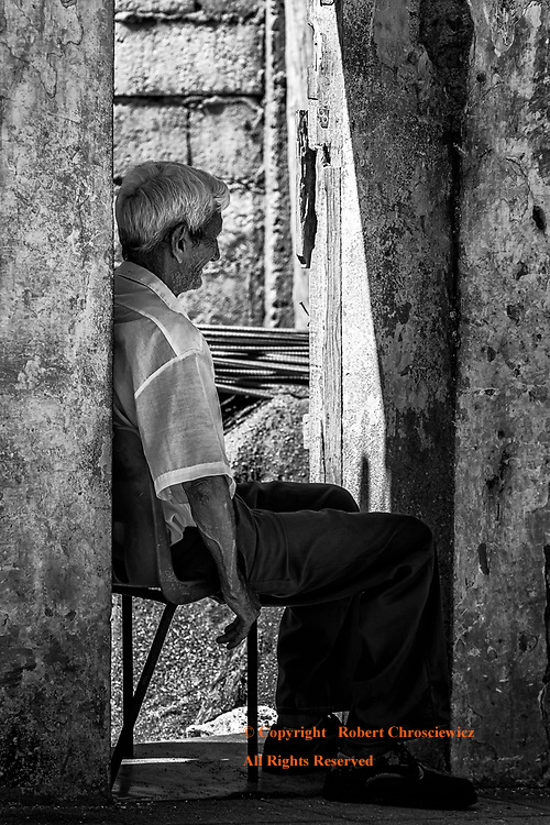 Wall Gazing (B&W): An old and lonely man sits in the recess of a dilapidated building, staring at a blank wall, Baracoa Cuba.