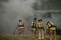 In-training firefighters from Gilford Fire department enter the Phelps Barn during controlled burn exercises at Gunstock on Saturday.  (Karen Bobotas Photo/for The Laconia Daily Sun)