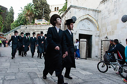 © Licensed to London News Pictures. 02/05/2014. Jerusalem, Israel. Young Jewish men hurry through the Armenian Quarter of the Old City of Jerusalem past the Armenian Catholic Chapel at approx 6.30pm in order to reach The Western Wall  in time for the start of the Shabbat (the Jewish sabbath).  Jewish custom sees the lighting of candles scheduled for 6.39pm this evening, shortly before the sunset when Shabbat commences.  The Western Wall is the most important shrine of the Jewish faith and is located in the Old City at the foot of the western side of Temple Mount. The Old City is comprised of four Quarters - the Jewish, Muslim, Christian and Armenian.  Photo credit : Richard Isaac/LNP