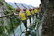 YICHANG, CHINA - MAY 24: (CHINA OUT) <br /> <br /> More than ten yoga enthusiasts perform yoga on a 236-meter-long glass plank road on May 24, 2016 in Yichang, Hubei Province of China. The glass plank road along a 7,500-meter-long cliff plank road is attractive in Yichang City. <br /> ©Exclusivepix Media