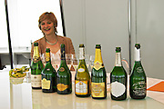 Delphine Geraud, oenologue enologist at the CIVC and a row of champagne bottles from different producers in the region at the Maison de la Champagne (the House of the Champagne Region), the head quarters of CIVC (Comite Interprofessionnel du Vin de Champagne) in Epernay, Champagne, Marne, Ardennes, France