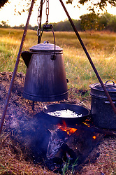 Stock photo of food cooking and water boiling on a campfire
