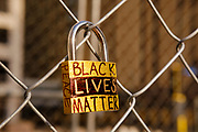 """02 APRIL 2021 - MINNEAPOLIS, MINNESOTA: A lock with """"Black Lives Matter"""" on it locked to the perimeter fence around the Henneping County Courthouse. The lock is one of hundreds of locks bearing the names of people of color killed by police on the fence. The installation is called """"Locks 4 Stolen Lives"""". Protesters are keeping a 24 hour presence in front of the Hennepin County Courthouse in Minneapolis during the murder trial of former Minneapolis Police Officer Derek Chauvin. Chauvin is on trial for murdering George Floyd in 2020. Floyd's death, while restrained and in police custody, set off a summer of racial justice protests across the United States.       PHOTO BY JACK KURTZ"""