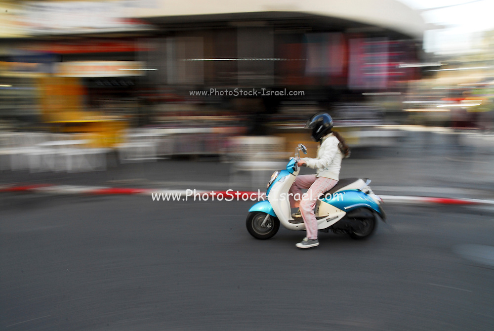 Urban scooter (moped) rider zooms past camera on a city street with motion blur affect