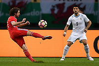 """Joe Allen, left, of Wales national football team kicks the ball to make a shoot against Luis Suarez of Uruguay national football team in their final match during the 2018 Gree China Cup International Football Championship in Nanning city, south China's Guangxi Zhuang Autonomous Region, 26 March 2018.<br /> <br /> Edinson Cavani's goal in the second half helped Uruguay beat Wales to claim the title of the second edition of China Cup International Football Championship here on Monday (26 March 2018). """"It was a tough match. I'm very satisfied with the result and I think that we can even get better if we didn't suffer from jet lag or injuries. I think the result was very satisfactory,"""" said Uruguay coach Oscar Tabarez. Wales were buoyed by a 6-0 victory over China while Uruguay were fresh from a 2-0 win over the Czech Republic. Uruguay almost took a dream start just 3 minutes into the game as Luis Suarez's shot on Nahitan Nandez cross smacked the upright. Uruguay were dealt a blow on 8 minutes when Jose Gimenez was injured in a challenge and was replaced by Sebastian Coates. Inter Milan's midfielder Matias Vecino of Uruguay also fired at the edge of box from a looped pass but only saw his attempt whistle past the post. Suarez squandered a golden opportunity on 32 minutes when Ashley Williams's wayward backpass sent him clear, but the Barca hitman rattled the woodwork again with goalkeeper Wayne Hennessey well beaten."""