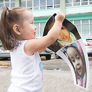 """CAPTION: Keren shows off her 'before' and 'after' photos, which show just how big a difference her cleft repair operations have made. Jaime says, """"other kids would always be so surprised when they saw her, and they would call her 'ugly'. They were just five to six years old, yet it would make us feel extremely sad. A month after her birth, we stopped hiding her because we realised we were so proud of her, and felt that this should come first"""". Keren had her first operation when she was five months old, and the second one when she was two. """"We realised before the first operation"""", Jaime continues, """"that the more we hide her, the more we made people believe she was something to be ashamed of. Taking her out and showing how proud we were of her made the situation easier to deal with"""". LOCATION: Hospital Escuela, Tegucigalpa, Honduras. INDIVIDUAL(S) PHOTOGRAPHED: Keren Sarahi Mijango Iriarte."""