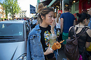 Young Asian woman holds her hand to her mouth with her snacks on Portobello Road in Notting Hill, West London, England, United Kingdom. People enjoying a sunny day out hanging out at the famous Sunday market, when the antique stalls line the street.  Portobello Market is the worlds largest antiques market with over 1,000 dealers selling every kind of antique and collectible. Visitors flock from all over the world to walk along one of Londons best loved streets.